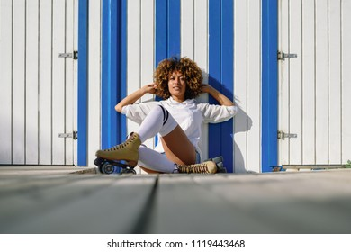 Young black woman on roller skates sitting near a beach hut. Girl with afro hairstyle rollerblading on sunny promenade.