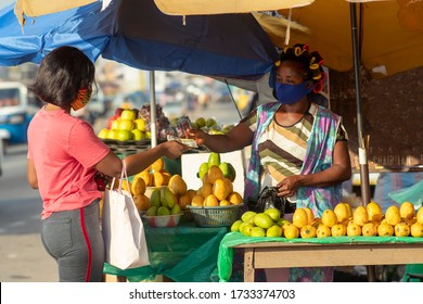 Young black woman paying money to a fruit vendor for a purchased item in the market. Two women wearing locally made masks on the street in covid-19 pandemic season for protection - Marketing in Africa