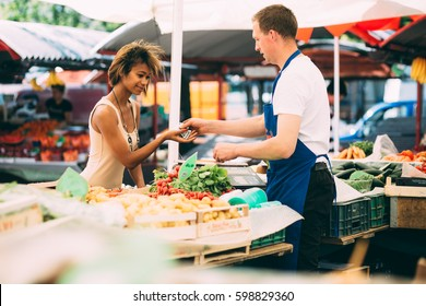 Young black woman paying for vegetables at farmer's market