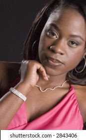 Young black woman in pink dress and jewelry resting chin on fingers