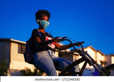 Young black woman with black power hair wearing protective mask and headphones on a lowrider bike
