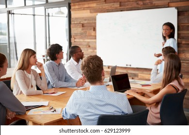 Young black woman presenting to colleagues from whiteboard