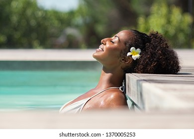Young black woman relaxing at spa pool. Beautiful woman relaxing in outdoor spa swimming pool with head leaning at poolside. Closeup face of attractive girl with closed eyes enjoy vacation at resort.