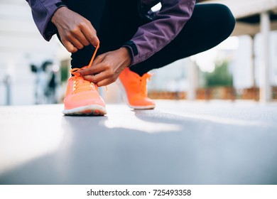 Young black woman runner tying sport shoes on street
