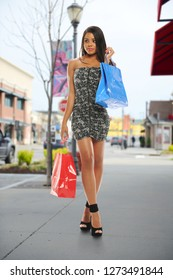 Young black woman with shopping bags outside the mall