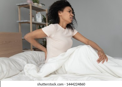 Young black woman sit on bed touching sore back feel morning backpain, upset african girl suffer from lower lumbar discomfort muscle pain waking up with backache after sleep on uncomfortable mattress