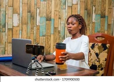 young black woman sitting at home, vlogging with her smartphone while working on her laptop