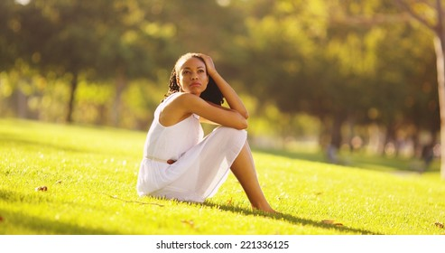 Young Black woman sitting in a park thinking