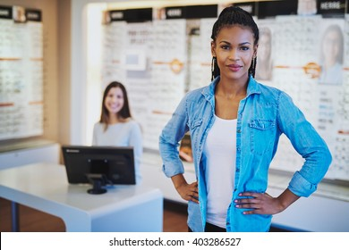 Young black woman smiling standing in her store with a colleague in backgorund