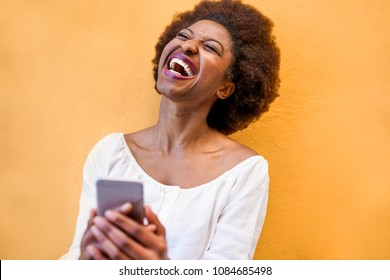 Young black woman standing isolated over yellow background using smart mobile phone - African girl laughing and smiling using web app on cellphone - Youth lifestyle and technology concept