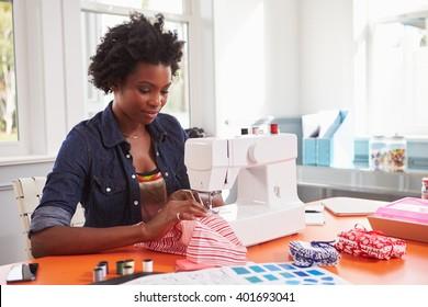 Young black woman stitching fabric using a sewing machine