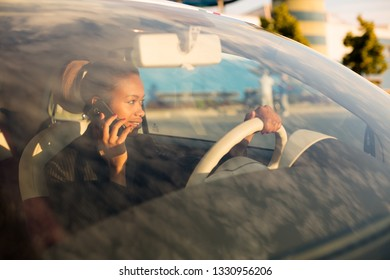 Young black woman talking on phone in car