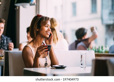 Young black woman talking on the phone in coffee shop