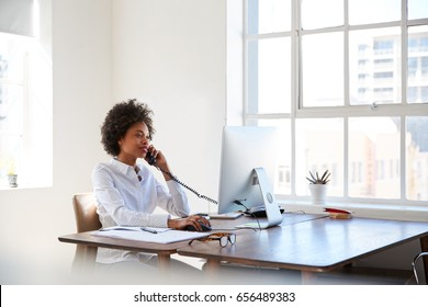 Young black woman talking on phone at her desk in an office