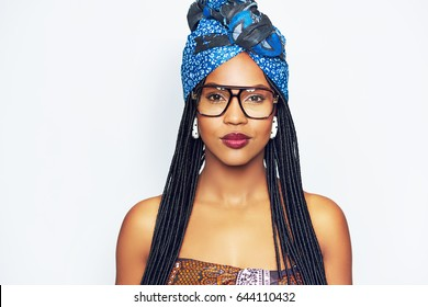 Young black woman in trendy blue headscarf and glasses with long braided hair