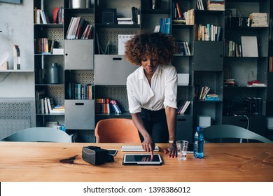 young black woman using tablet in modern office – concentration, inspiration, resourceful