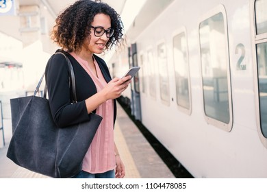 Young black woman waiting for the train on station platform