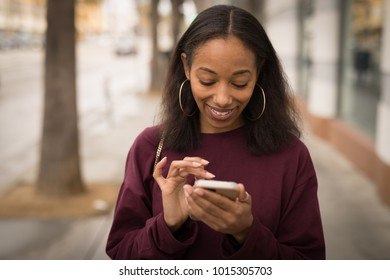 Young black woman walking typing on cell phone