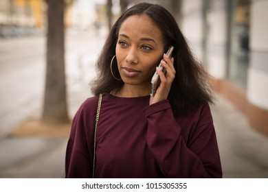 Young black woman walking using cell phone