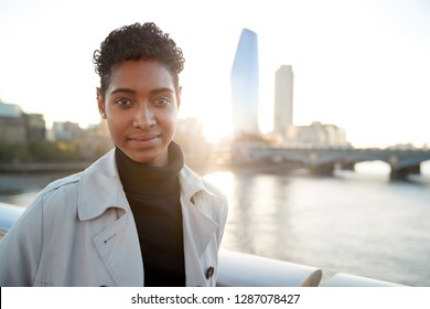 Young black woman wearing a turtleneck sweater and a mackintosh standing on Millennium Bridge, London, looking to camera smiling