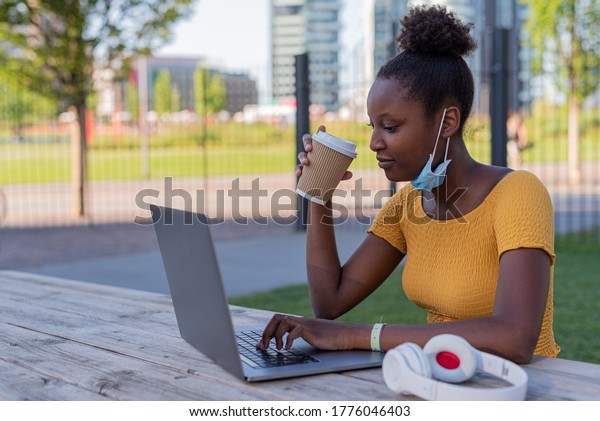 young black woman at work on her laptop in times of epidemic outdoors, use of protective mask, young student at the park