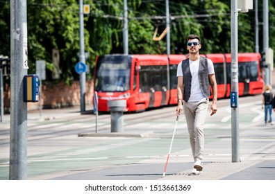 Young blind man with white cane walking across the street in city.