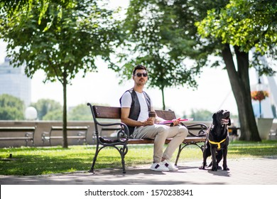 Young blind man with white cane and guide dog sitting in park in city.