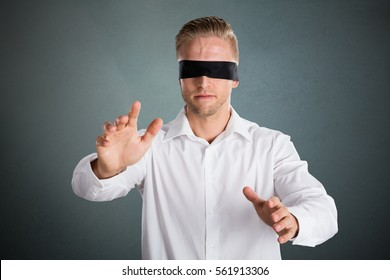 Young Blindfolded Lost Businessman Against Grey Background