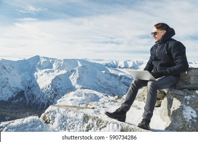 Young blogger or freelancer working on a laptop on top of the world. Winter lanscape in sunny day.