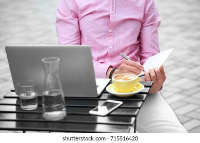 Young blogger with laptop working at table, outdoors