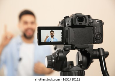 Young blogger shooting video with camera against beige background, focus on screen