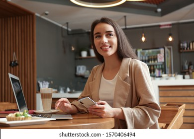 Young blogger with smartphone and laptop in cafe