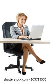 A young blond attractive businesswoman in skirt sitting at her desk and looking attentively at her laptop, full figure with legs is shown - isolated on white