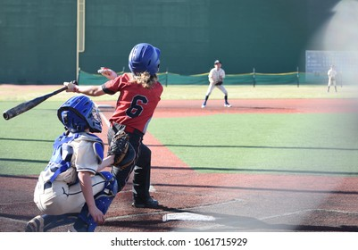 Young blond baseball player at bat in well manicured stadium field