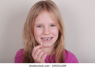 Young blond beautiful girl lost her first bottom front milk teeth. Childhood healthcare concept.