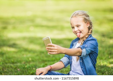 Young blond beautiful girl putting out her tongue making a selfie sitting on green grass