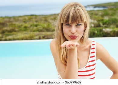 Young blond beauty blowing a kiss by pool