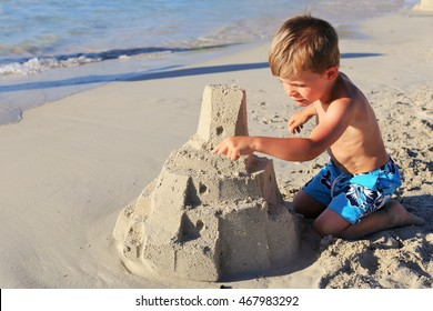 A young blond boy building sand castle in a beach in Corsica