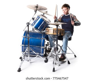 young blond boy at drum kit in studio against white background