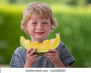 Young Blond Boy Eating Yellow Watermelon