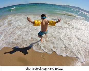 A young blond boy jumping with his armband into the waves of a sea. Rounded sea and horizon with a vintage tone.