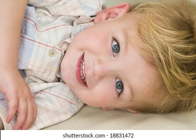 A young blond boy laying down and giving a cheeky grin