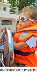 A young blond boy navigating on a small motor boat