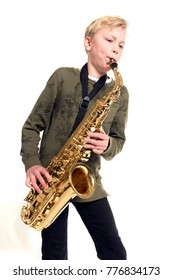 young blond boy and saxophone in studio against white background