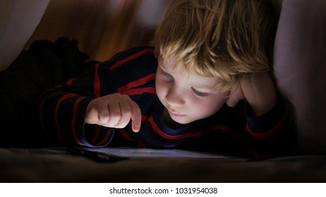 Young blond boy under covers playing on tablet a computer game.