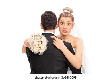 Young blond bride hugging her husband with her fingers crossed isolated on white background