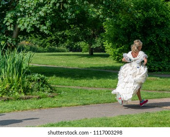 Young blond bride in white wedding dress and training shoes runs away through the park.