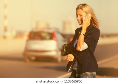 Young blond business woman calling on cell phone  Stylish fashion model in dark blue blazer and jeans outdoor