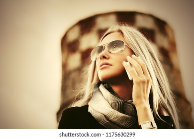 Young blond business woman in sunglasses calling on cell phone walking outdoor Stylish fashion model wearing black blazer and gray scarf