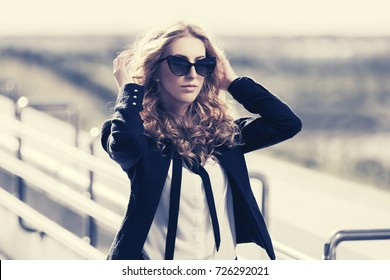 Young blond business woman in sunglasses walking in city street. Stylish female model in black jacket outdoor